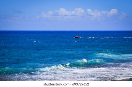 Speedboat running on the sea at Le Morne in Mauritius. Mauritius is some 2,000 km (1,200 mi) off the southeast coast of Africa.