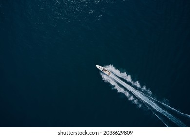 Speedboat wave speed water. Speedboat movement on the water. Large white boat driving on dark water. Speedboat on dark blue water aerial view.