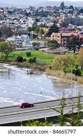Speeding car crossing Patterson Bridge with floodwater, Launceston, Tasmania, Australia