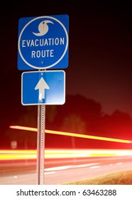 Speeding cars flee an impending storm at night along a hurricane evacuation route.