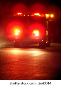 Speeding fire truck with flashing emergency warning lights driving fast to a disaster response scene on a street at night