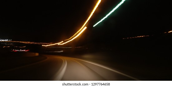 Speeding lights blur of road at night.
