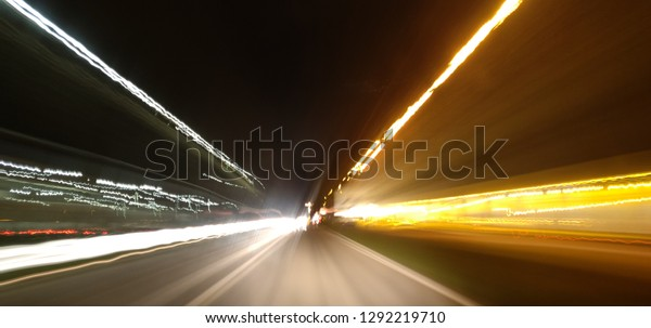 Speeding lights blur of road at night.