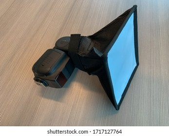 A speedlight with a mini softbox to diffuse the flash light.