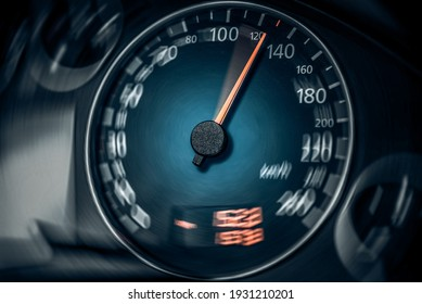 The speedometer of a modern car shows a high driving speed. Added motion blur.