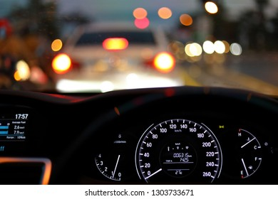 speedometer in modern vehicle car drive travel road trip in night city with blur bokeh traffic light on street background