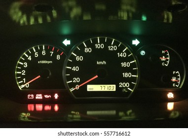 Speedometer on car dashboard with hazard signal led light on battery brake door and engine