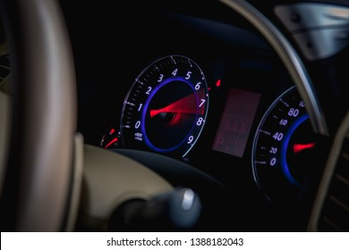 Speedometer scoring high speed in a fast motion. Sporty Car Dashboard Instruments illuminated at night. Rev counter. Modern Vehicle cluster