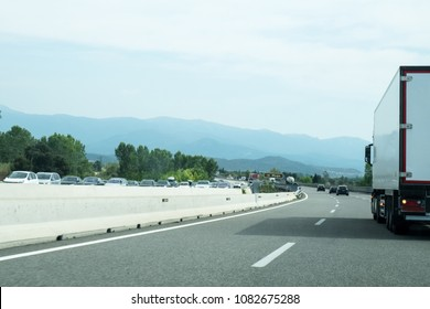 The speedy highway road of France often has a buzy traffic motion of cargo vans, trucks, cars, buses and combies.