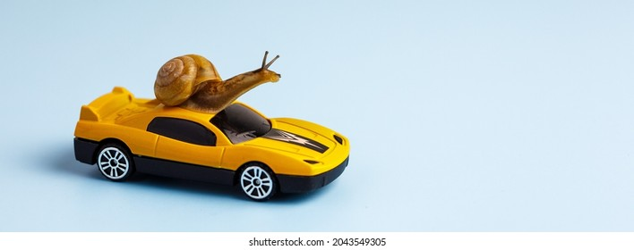 Speedy snail like car racer. Concept of speed and success. Concept of fast taxi or delivery. Yellow race car on light blue background. Banner, copy space