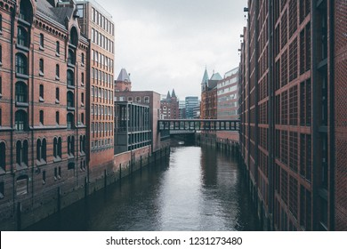 Speicherstadt (City of Warehouse) with steel bridge and the canal in cloudy day, Hamburg