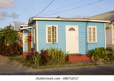 Speightstown, Barbados - April 6, 2017: Colour in Barbados. A local house is painted a bright blue that glows in the light of the setting sun. Bajans are known to love colour.