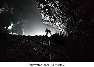 Speleologist descend by the rope in the vertical cave tunnel from  entrance light to dark.  Monochrome silhouette image. Cave Cascadnaya. Plateau of the Ai Petri. Crimea. Russia.