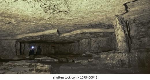 Speleologist in a huge hall. The Cave of Zedekiah. quarries of King Solomon, located under the Temple Mount. Stones, dark vaults, side lighting.
