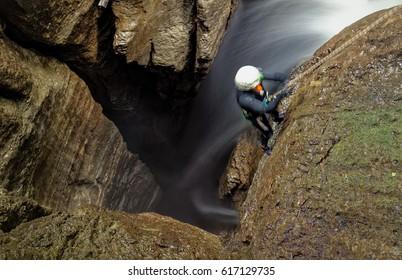 Speleologist Inside Deep Waterfall Entrance Shaft At Mayei Cave In Ecuadorian Amazonia Blurred Motion