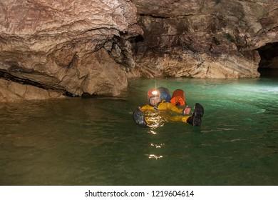 Speleologist swimming with two bags in underground river. Karst cave Leningradskaya. Caucasian mountains. Abkhazia.