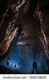 Speleologists wondering and admiring a gigantic cave chamber. Caving is a science and extreme sport dedicated to discover new underground unexplored passages