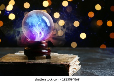 Spell book and crystal ball of fortune teller on table