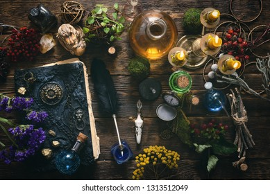 Spell book, magic potions and other various witchcraft accessories on the wizard table background.