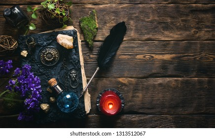 Spell book, magic potions and other various witchcraft accessories on the wizard table background with copy space.