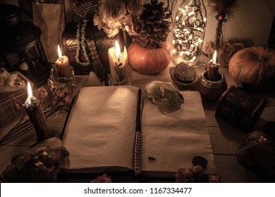 Spellbook, sorcery for Halloween, pumpkin, tarot cards and burning candles, Wicca