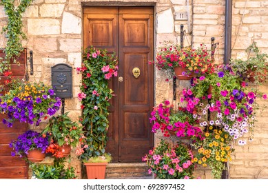 SPELLO, ITALY - MAY 27, 2017 - Close up of a door of a residential building in Spello decorated with colorful flowers.