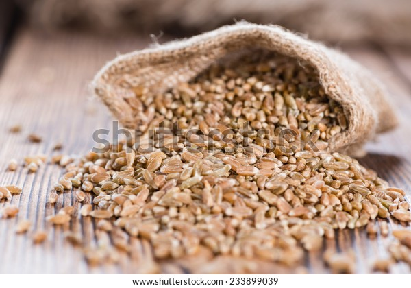 Spelt (detailed close-up shot) on an old dark wooden table