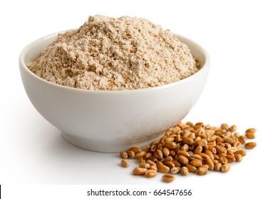 Spelt whole grain flour in white ceramic bowl isolated on white. Spilled winter wheat kernels.