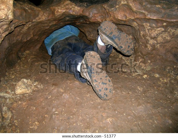 Spelunker crawling through a cave
