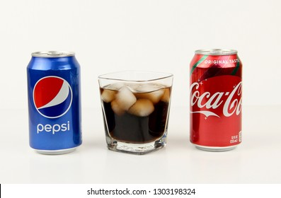 Spencer, Wisconsin, February, 3, 2019   Cans of Pepsi and Coke next to a glass of ice
