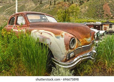 SPENCES BRIDGE, CANADA - MAY, 24, 2017: Roadside vintage car at Vulture Garage, a store for vintage cars and antiques at Spences Bridge, BC, attracting visitors travelling on Trans Canada Highway.