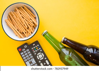 Spend an evening relaxing and watching movie with friends or family. A bowl of bread sticks, two bottles of dark and light beer and two remote controls on a bright yellow background. Close up
