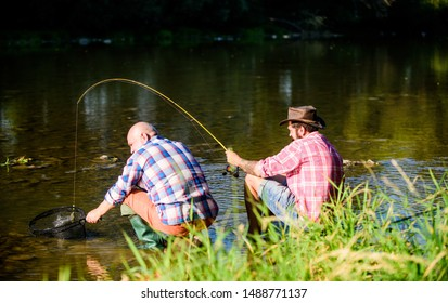 spend time together. fly fish hobby of men. retirement fishery. happy fishermen friendship. big game fishing. relax on nature. retired father and mature bearded son. Two male friends fishing together.