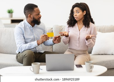 Spender. Angry black husband holding credit card, blaming his wife for overspending and wasting too much money on online shopping, couple arguing about budget expenses having financial problems, debt