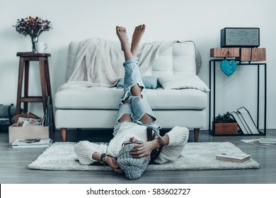 Spending carefree time. Beautiful young woman in casual wear touching her head with hand while lying on the floor at home