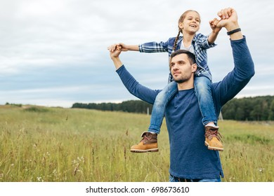 Spending family time together. Happy father giving piggyback to his little daughter while having stroll across beautiful nature landscapes. Smiling daughter and her daddy having good relationships
