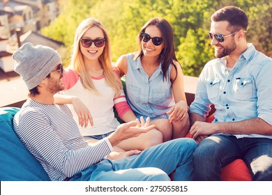 Spending great time with friends. Top view of four young cheerful people chatting while sitting at the bean bags on the roof of the building
