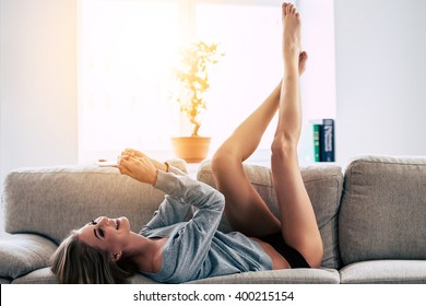 Spending great time at home. Beautiful young woman using smartphone with smile while lying on sofa at home