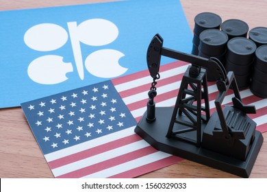 Spending or investment of a country's revenues from petroleum exports industry (Petrodollar). Oil pump jack on U.S. and OPEC flag background. Concept of U.S. crude oil production, petroleum industry.
