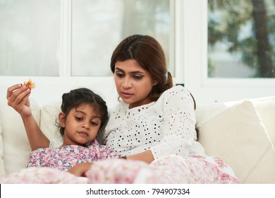 Spending lazy weekend at home: pretty Indian woman and her cute little daughter lying on cozy sofa, eating delicious pastry and watching cartoon on digital tablet