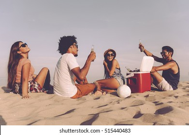 Spending nice time with friends. Rear view of four cheerful young people spending nice time together while sitting on the beach and drinking beer