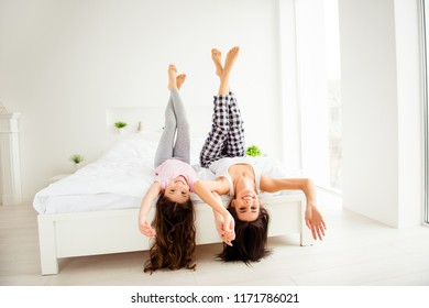 Spending spare time together. Cheerful positive glad charming beautiful mom and her sweet nice small little daughter, lying on bed upside down, raising legs up, holding hands in light white interior