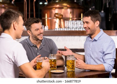 Spending time in bar. Three cheerful friends drinking beer in bar