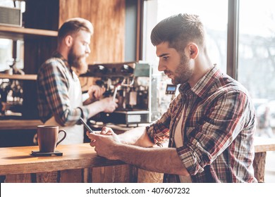 Spending time at coffee shop. Side view of young handsome man using his smartphone while sitting at bar counter at cafe with barista at the background