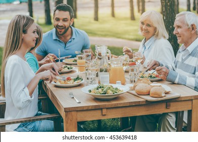Spending time with family. Happy family of five people communicating and enjoying meal together while sitting at the dining table outdoors