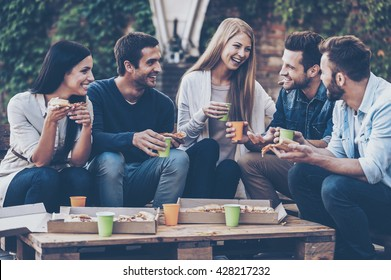 Spending time with friends. Group of cheerful young people talking to each other and eating pizza while sitting outdoors