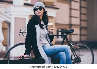 Spending time outdoors.  Side view of beautiful young woman in sunglasses holding coffee cup and looking away while sitting on bench outdoors