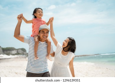 spending time with their daughter enjoy holiday walking around the beach in the sun