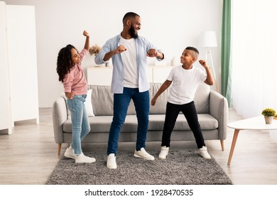 Spending Time Together Concept. Cheerful black dad moving and dancing to music with his excited daughter and son. Playful children having fun with father, enjoying weekend with family in living room