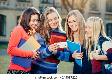 Spending time together. Four smiling female students discussing something and looking at the smartphone while standing together in campus